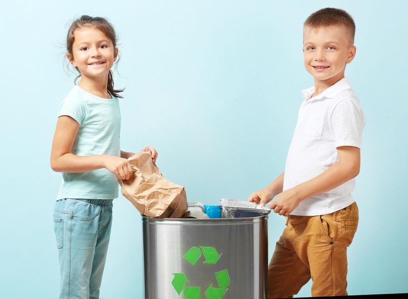 Crianças depositam recicláveis em lixeira de inox