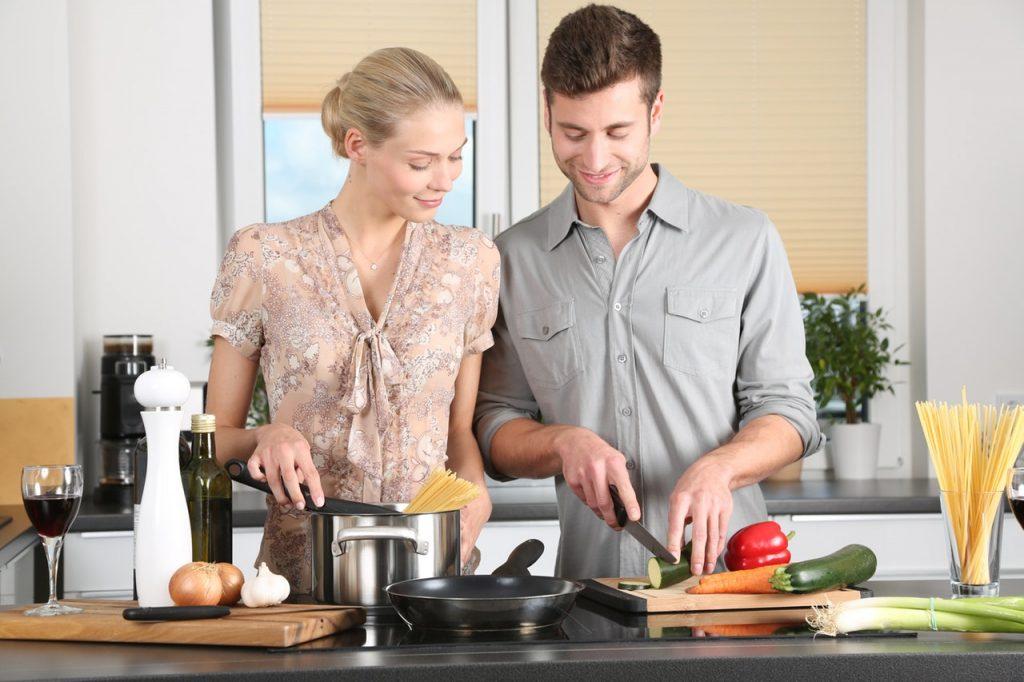 Na foto um casal cozinhando legumes e macarrão.