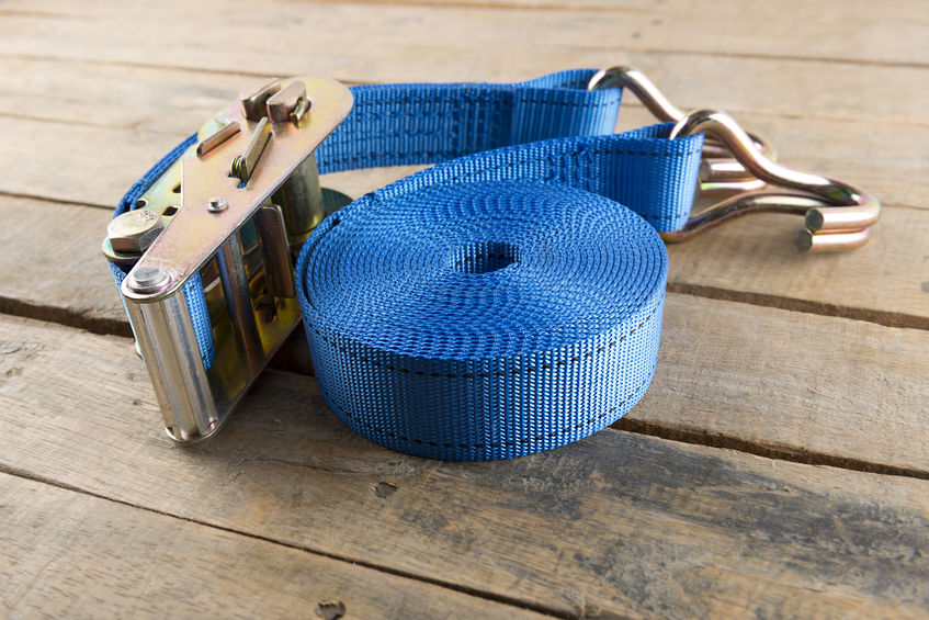 Cinta de amarração azul enrolada posicionada sobre a madeira