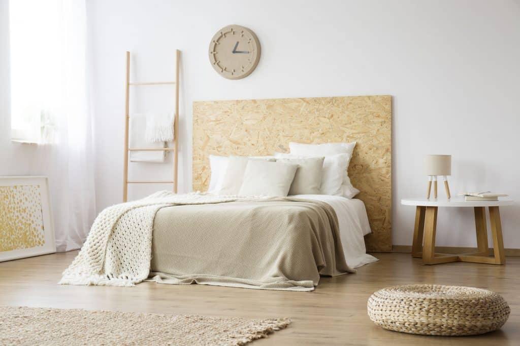 Imagem de cama king size em quarto amplo com mesa de cabeceira aos lados e relógio na parede.