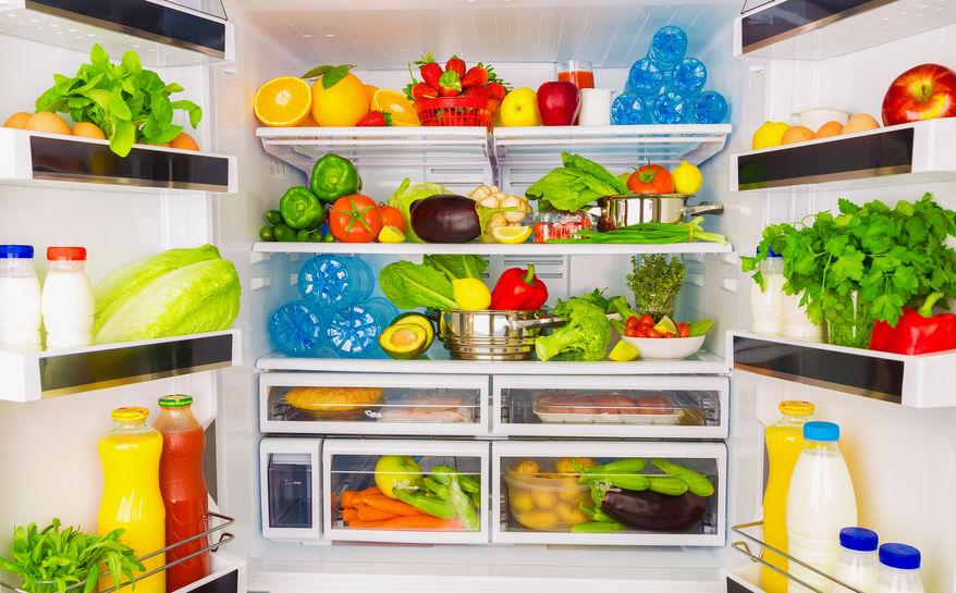 Frutas e legumes na gaveta da geladeira com luz azul.