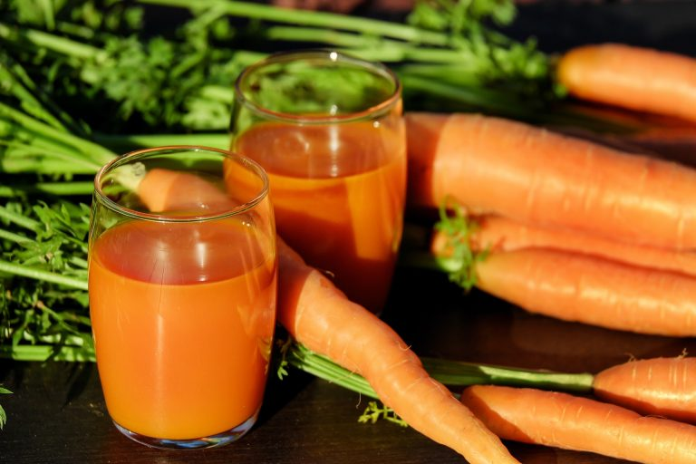 Imagem de sucos naturais com cenouras ao fundo