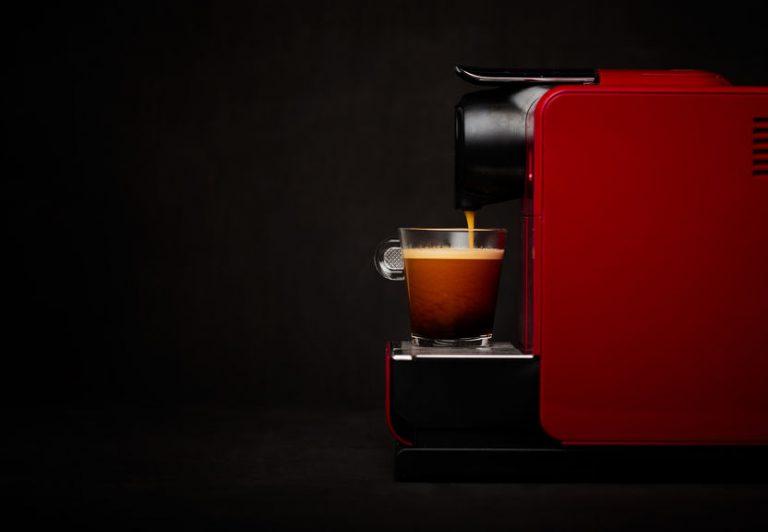 Máquina de café em cápsulas preparando xícara de café preto.