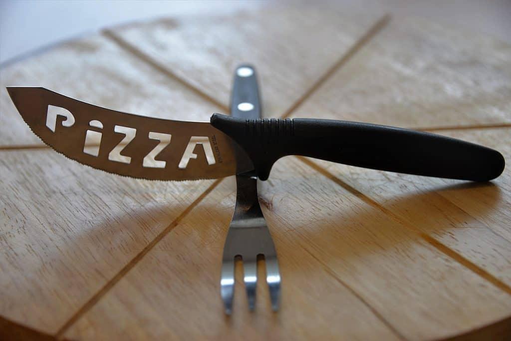 Faca curva para pizza apoiada sobre garfo em tábua para pizza.