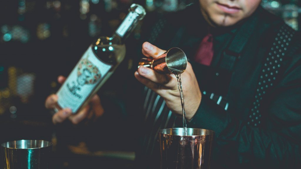 Um barman segura em uma das mãos uma garrafa de bebida alcoólica enquanto na outra despeja o líquido de dentro de um dosador para dentro de um copo.