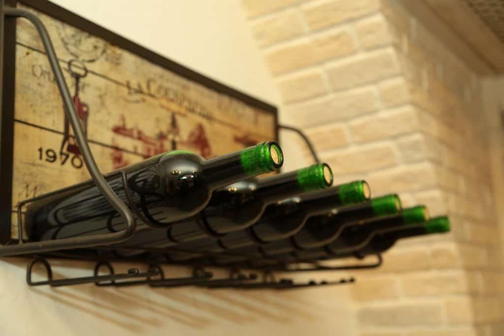 Suporte para vinho de parede, com garrafas de vinho em cima.