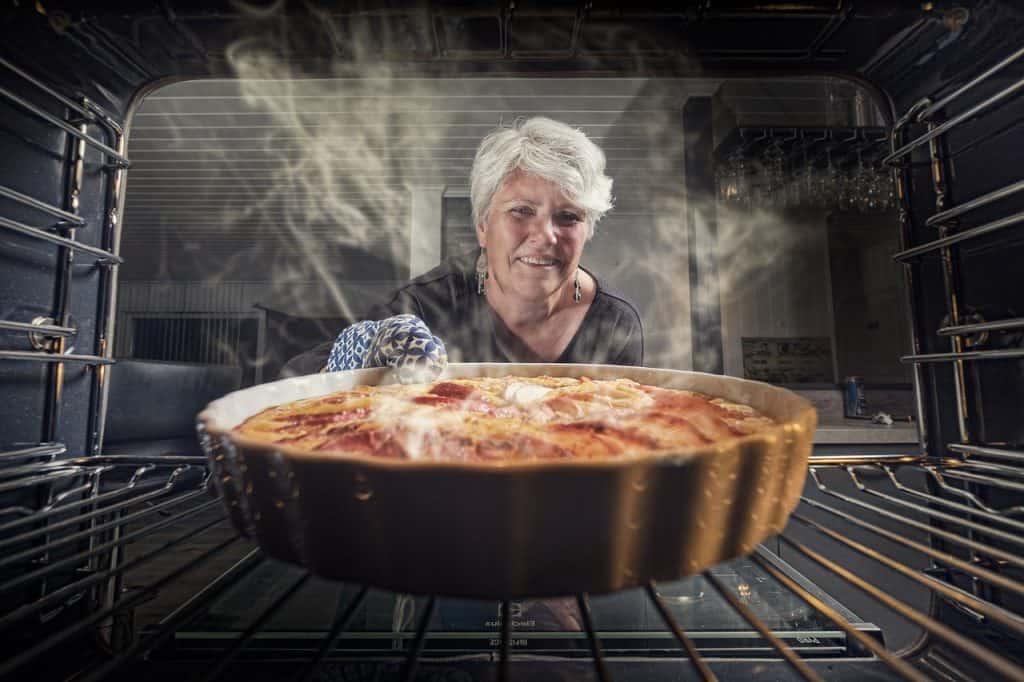 Uma senhora idosa retira uma forma com uma torta de dentro de um forno.