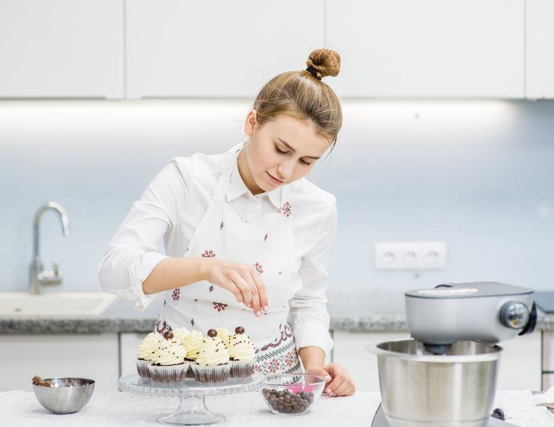 Moça decora cupcakes em bancada ao lado de batedeira