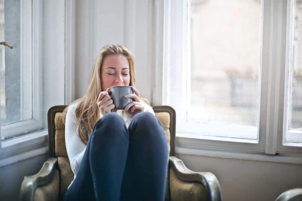 Uma mulher loira está sentada, de olhos fechados, em uma poltrona com as pernas por cima e dobradas. Ela segura uma caneca de cerâmica com as duas mãos.