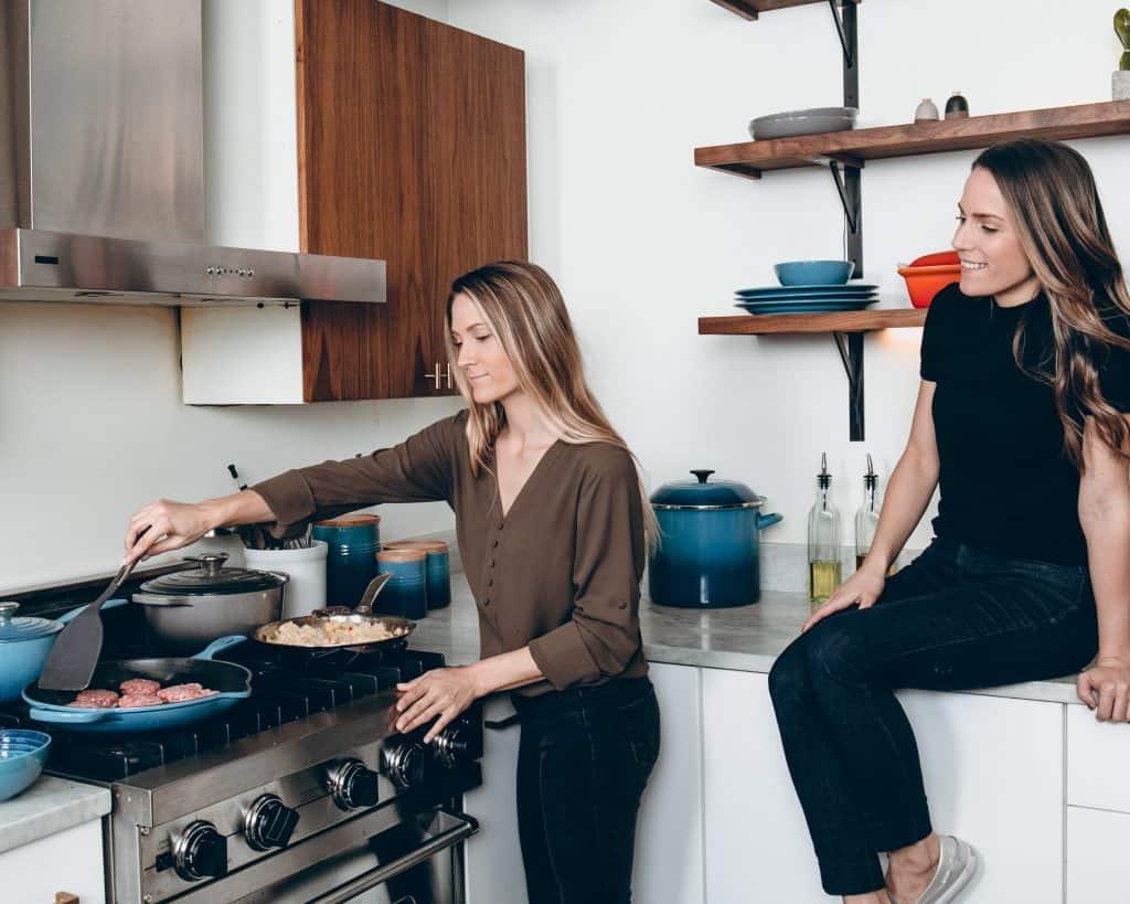 Imagem de uma mulher preparando hambúrgueres e outra sentada em uma bancada.