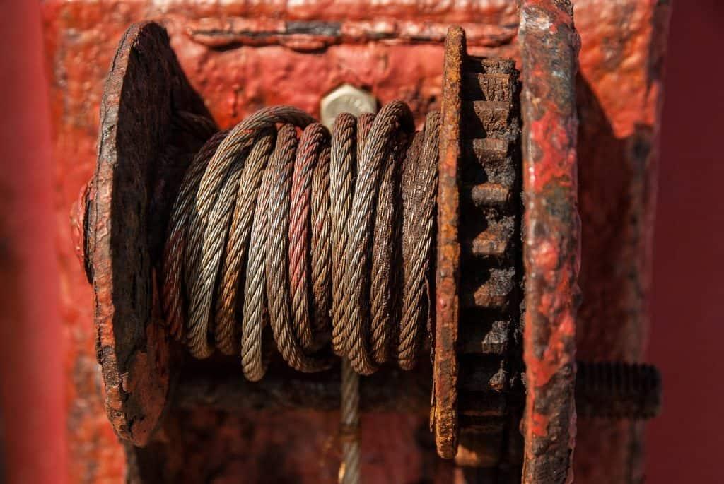 Imagem mostra , em plano detalhe, o cabo de aço de um guincho antigo, com marcas de ferrugem.