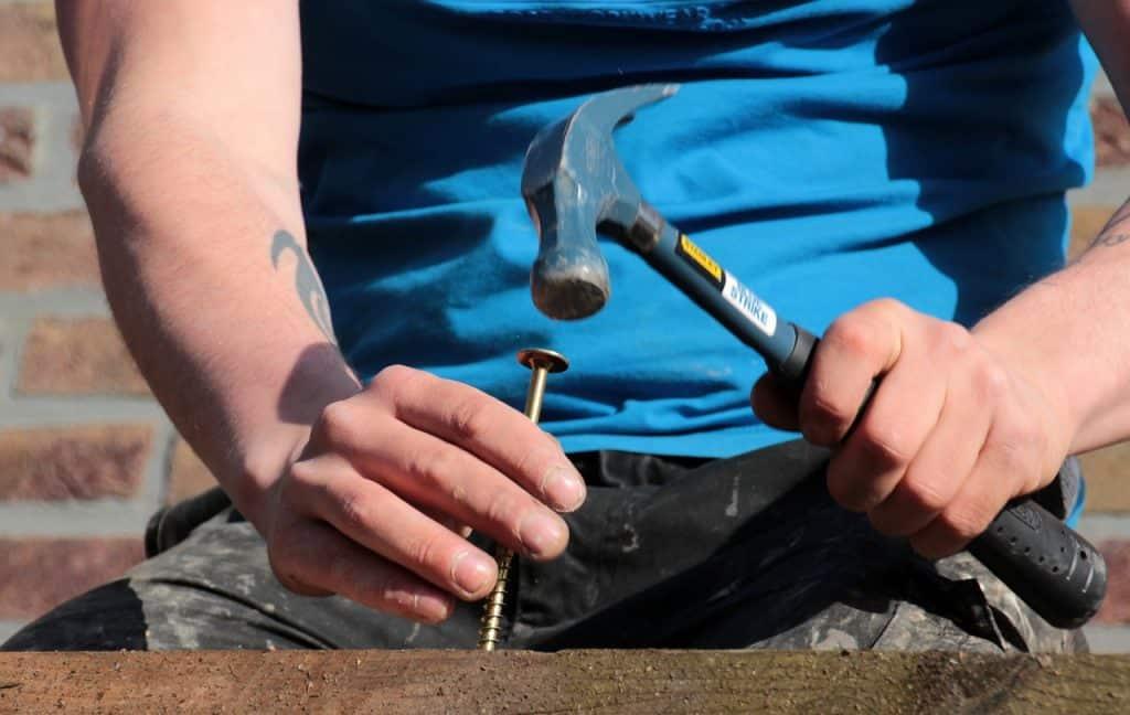 Um homem martelando um prego grande em uma tábua de madeira.