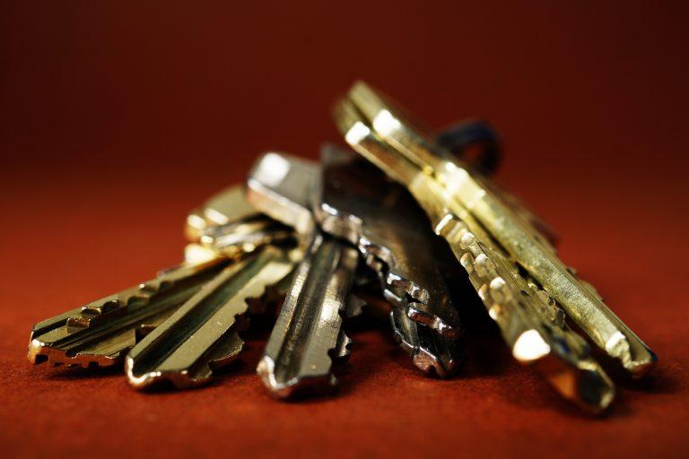 Imagem mostra num plano detalhe um molho de chaves sob um superfície lisa.