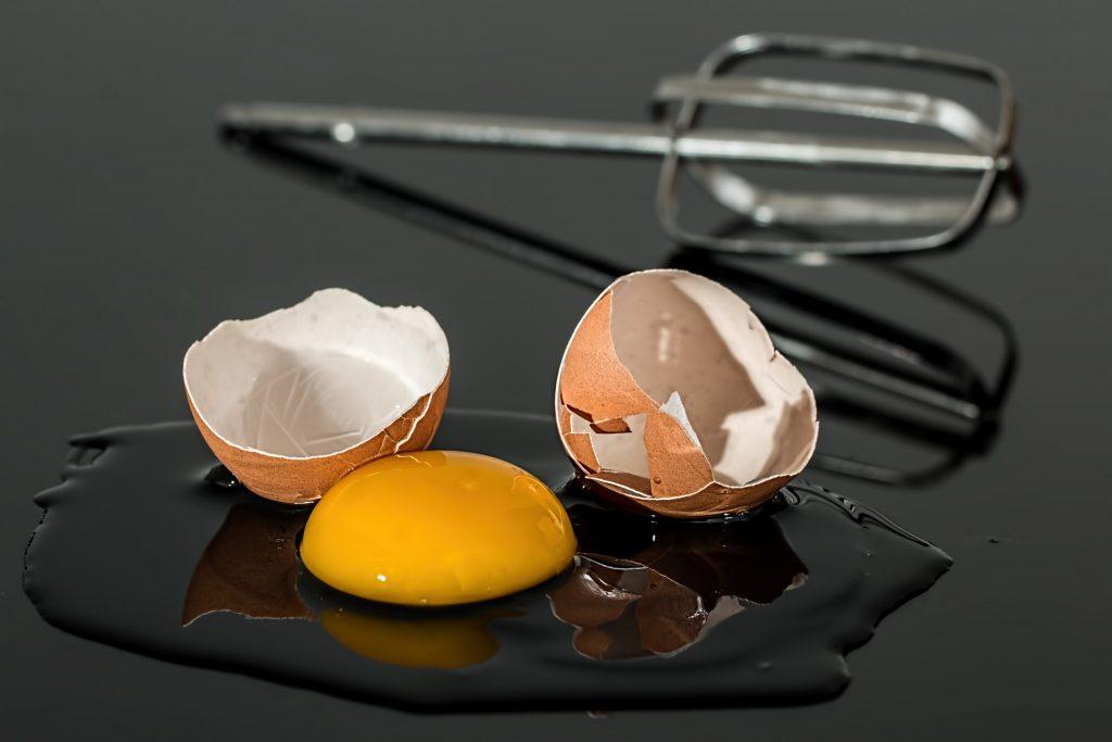 Imagem de batedor metálico atrás de ovo quebrado