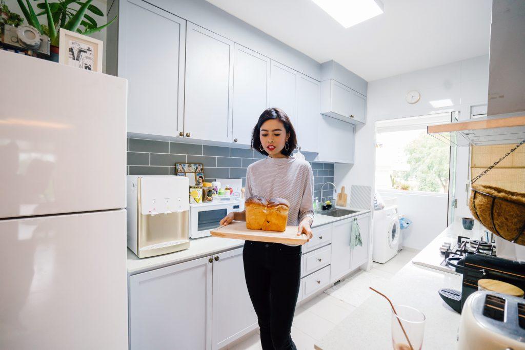 Imagem de uma mulher carregando uma travessa com pão.