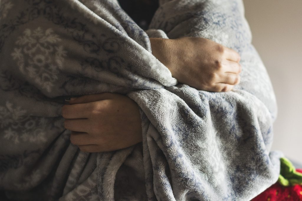 Na foto uma pessoa enrolada em um cobertor cinza.