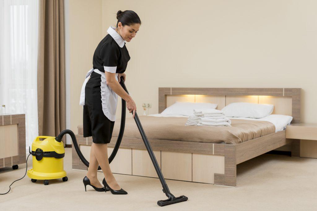 Funcionária aspira quarto de hotel com aspirador Wap
