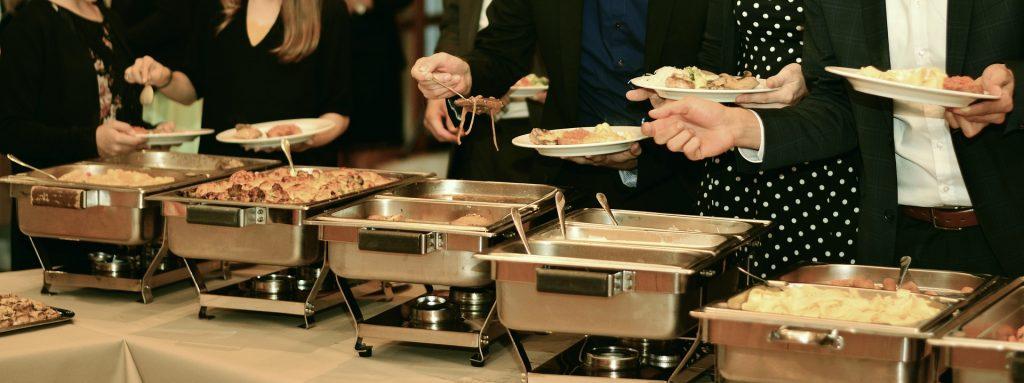 Imagem de pessoas servindo-se em buffet montado sobre a mesa.