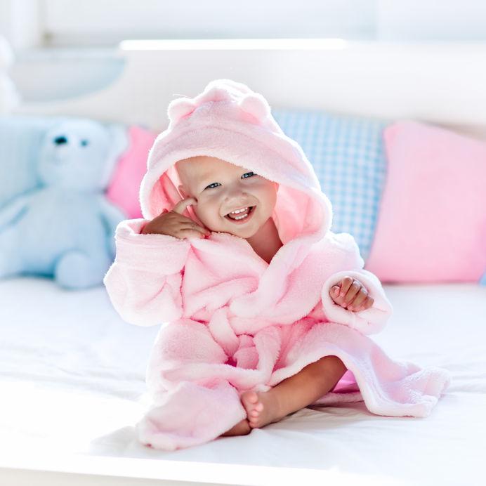 Bebê usando roupão em cima da cama sorrindo.