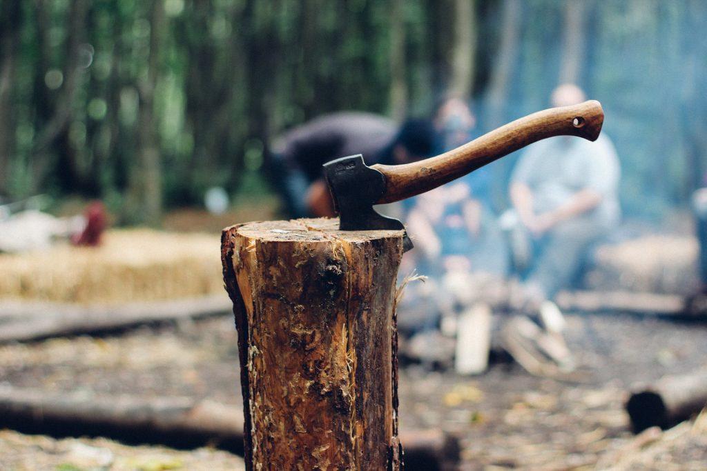 Um machado médio fincado em um pedaço de lenha