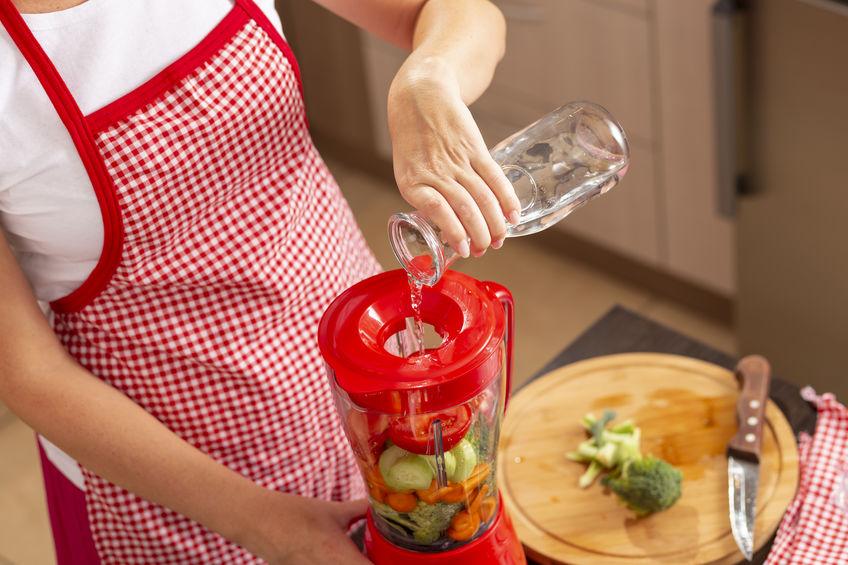 Mulher de avental vermelho colocando água em liquidificador para bater verduras.