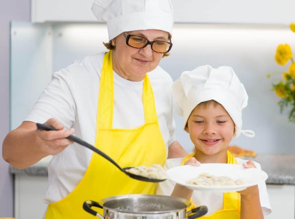 Avó e neto na cozinha preparando refeições juntos, eles estão usando avental amarelo, toca de cozinha e a avó está segurando uma escumadeira.