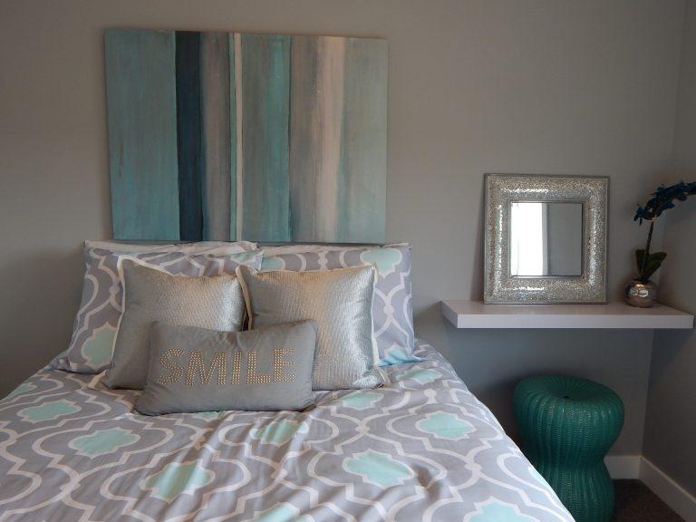 Quarto com cama box de casal, com quadro na parede e aparador ao lado com banquinho e espelho.