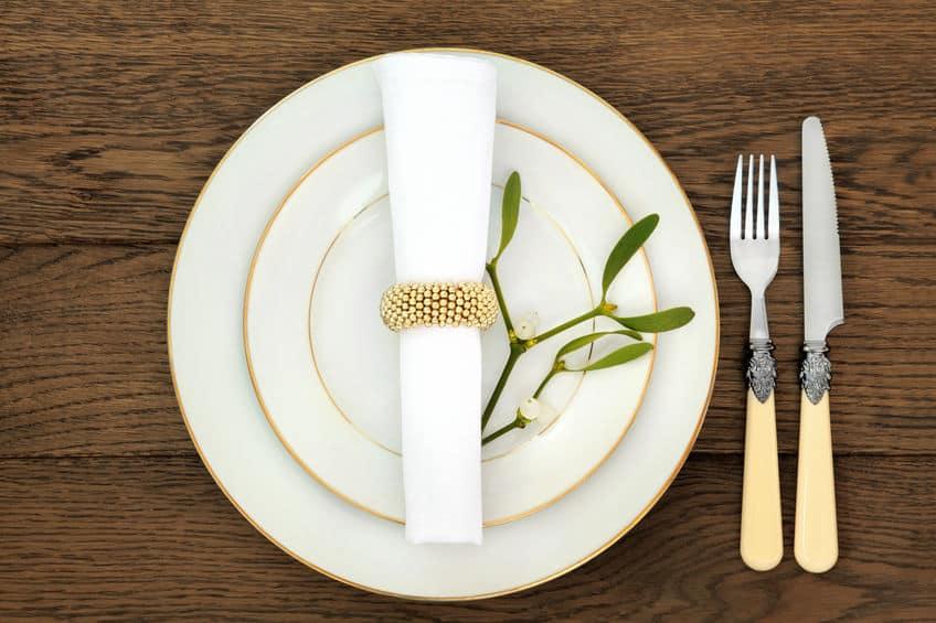 Imagem de prato com guardanapo sobre ele e talheres ao lado.