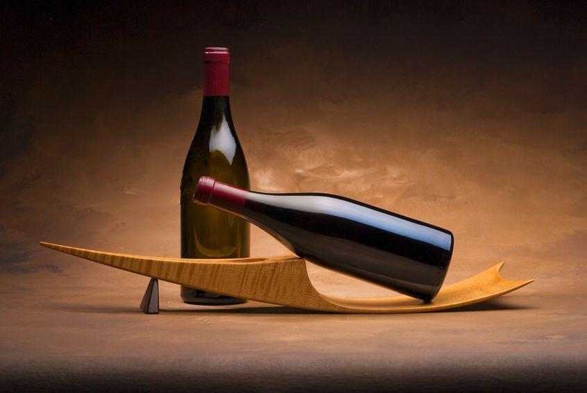Imagem de suporte para vinhos de madeira com design inovador e duas garrafas de vinho.