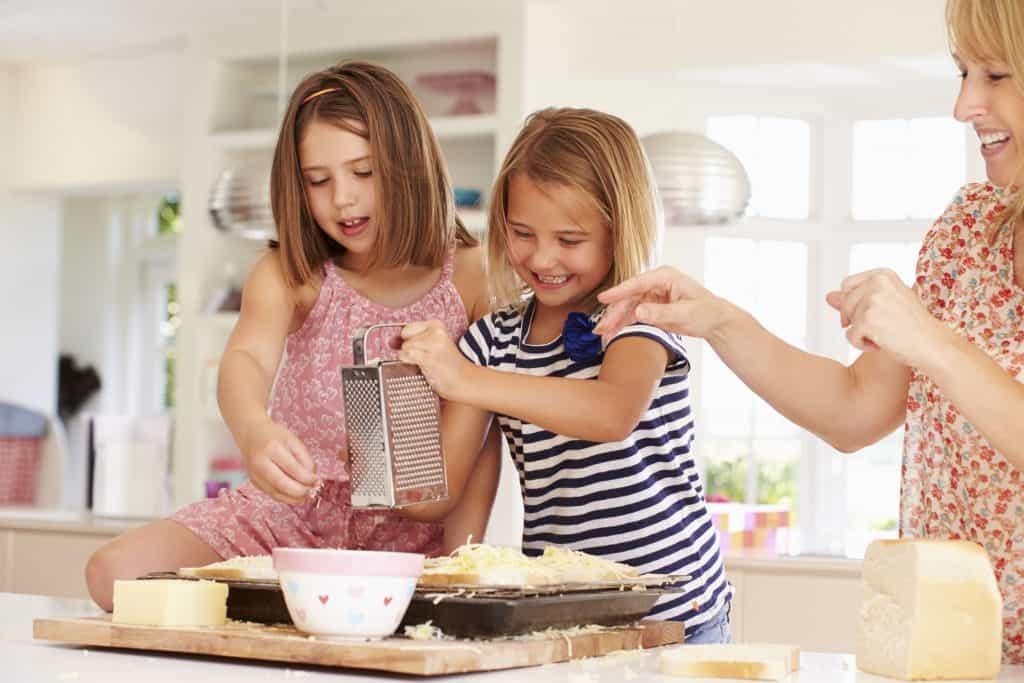 Na foto uma mulher com duas meninas ralando queijos dentro de uma cozinha.