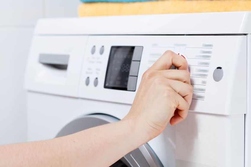 Na foto uma mão no botão de uma máquina de lavar.