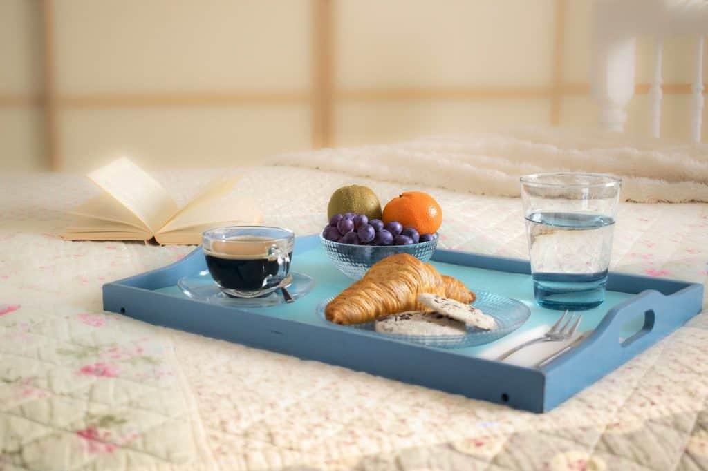 Bandeja de café sobre cama ao lado de livro.