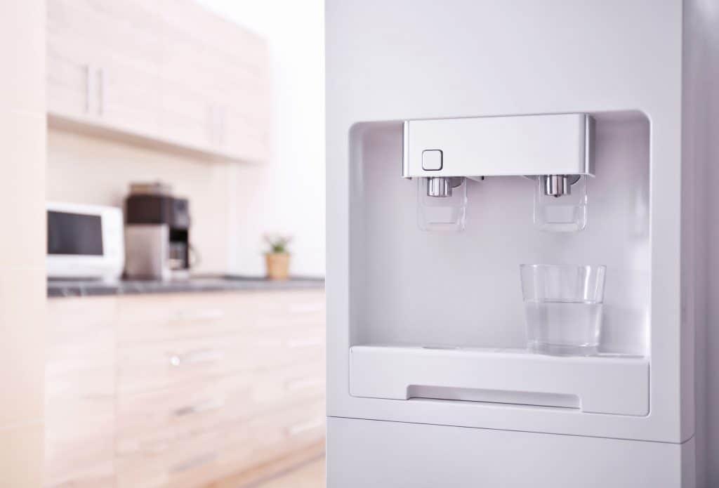 Na foto um purificador de água com um copo cheio e ao fundo uma bancada de cozinha.