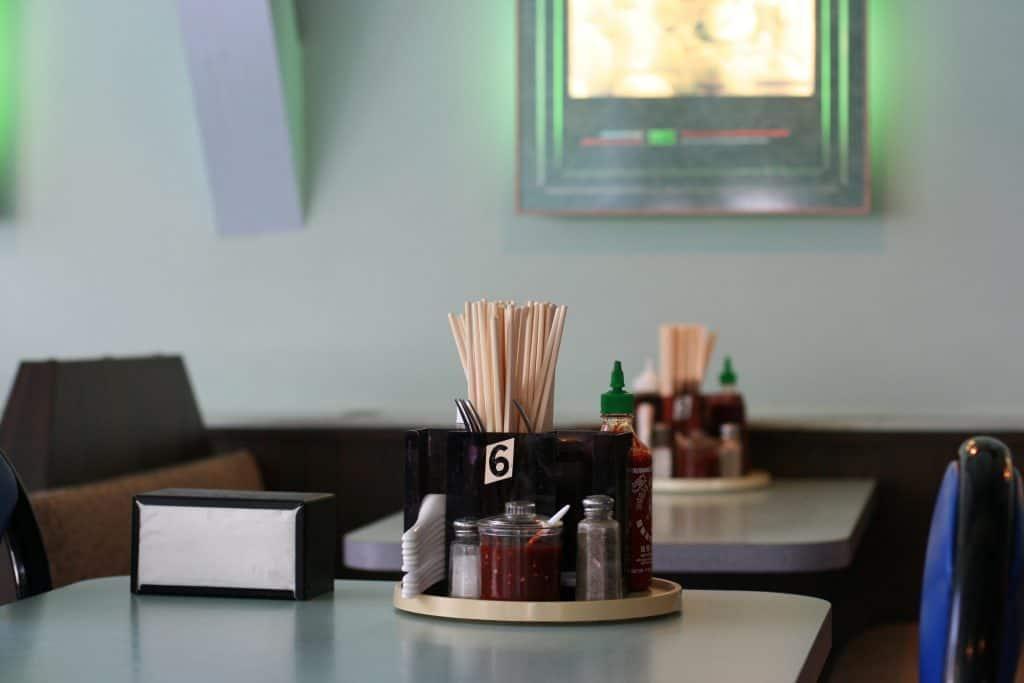 """Imagem mostra um dispensador de guardanapo na horizontal, ao lado de um """"kit"""" com molho de pimenta, saleiros, palitos de dente e pequenos talheres. Ambos estão sob uma mesa de madeira."""