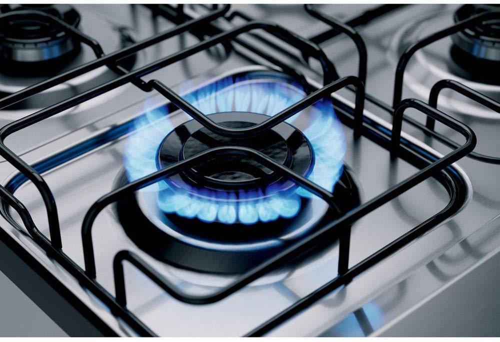 Detalhe de um queimador de fogão com a chama acesa.
