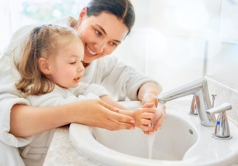 Mãe e filha de roupão lavando as mãos na pia do banheiro.