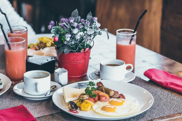 Na foto uma mesa posta com pratos, xícaras e dois copos com suco.