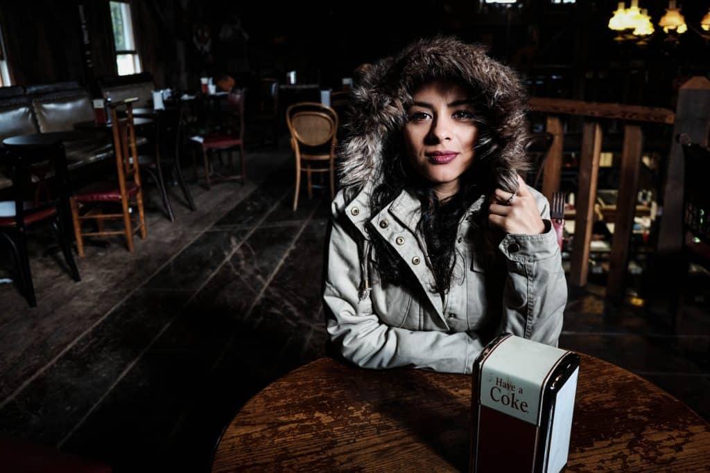 """Imagem mostra uma mulher agasalhada sentada à uma mesa de madeira com um porta guardanapo com os dizeres """"Beba Coca"""" . Ao fundo, um bar vazio, com mesas cadeiras e sofás desocupados."""