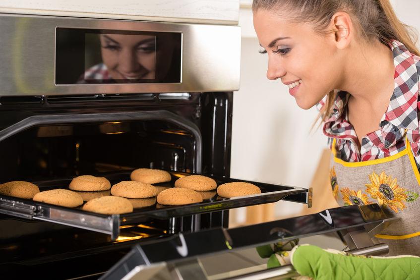 Imagem de uma mulher olhando uma forma de pães assados.