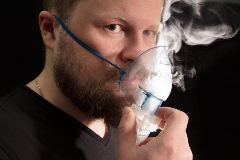 Na foto um homem fazendo inalação usando uma máscara no rosto.