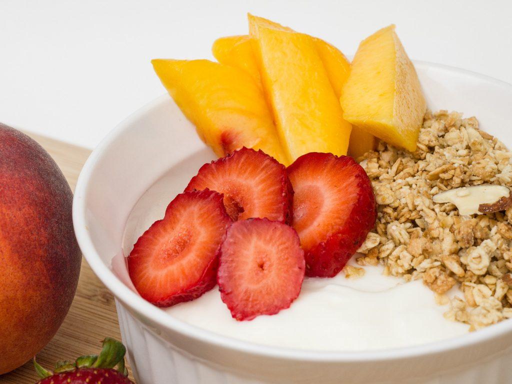 Imagem de pote de iogurte natural com pêssegos, morangos e granola