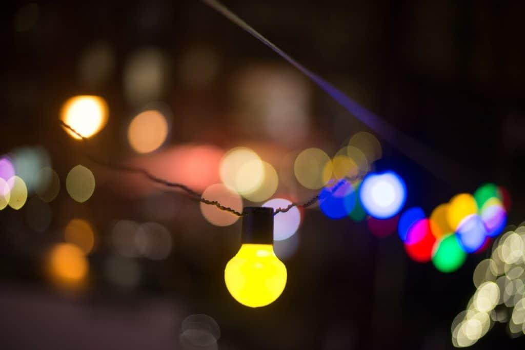 Na foto uma lâmpada amarela acesa pendurada em um fio preto.