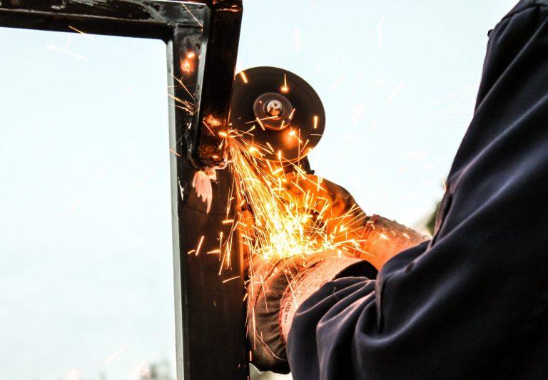 Imagem mostra uma esmerilhadeira angular sendo usada em uma peça de metal.