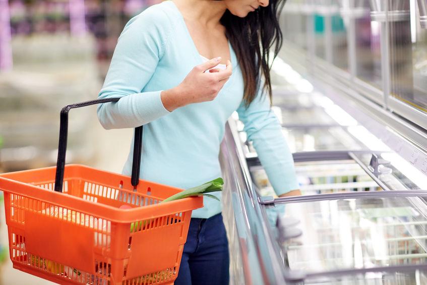 Moça escolhe congelados de freezer com tampa de vidro em supermercado