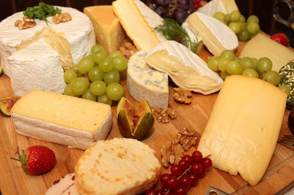 Na foto uma tábua com diversos tipos de queijo e uvas verdes.
