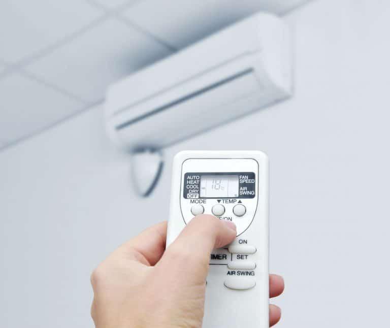 Na foto uma pessoa apontando um controle para um ar condicionado.
