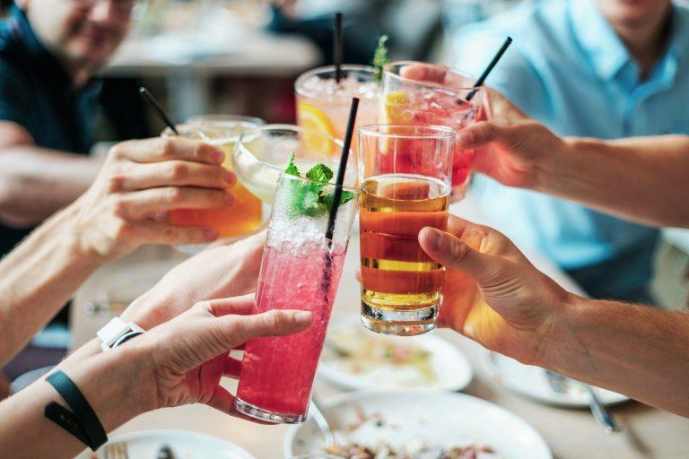 Na foto diversas pessoas brindando em uma mesa.
