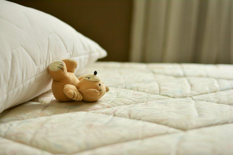 Colchão e travesseiro, sem lençol e sem fronha, com um ursinho de pelúcia sobre a cama.