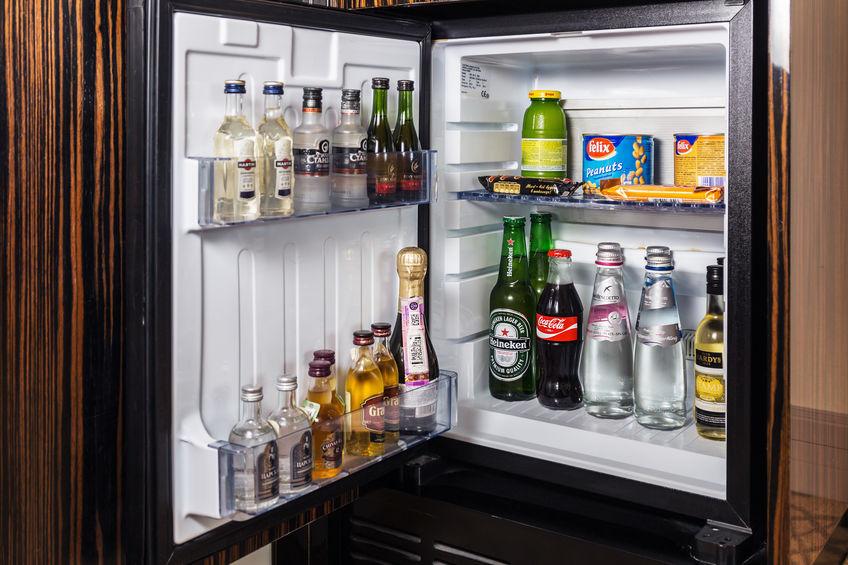 Frigobar aberto com bebidas e alimentos.
