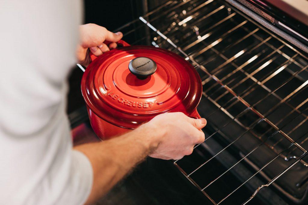 Na foto um homem colocando uma panela dentro de um forno.